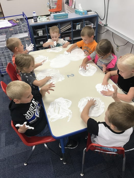 Students drawing with shaving cream.